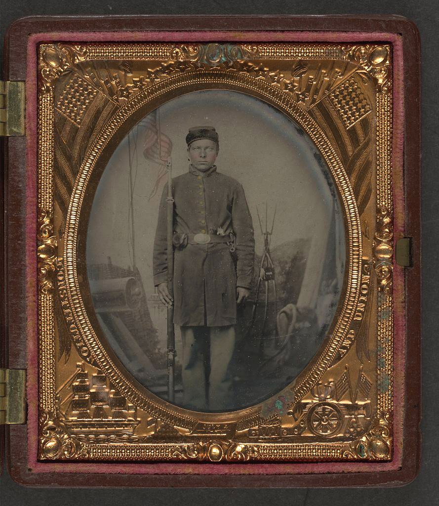 soldier in Union uniform with musket, bayonet in scabbard, revolver, and cap box in front of painted backdrop showing military camp scene LOC 5228569409.jpg