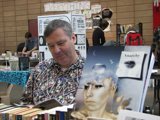 Bob Black seated at the ''[[Anarchy: A Journal of Desire Armed]]'' booth, attending the 2011 Bay Area Anarchist Bookfair