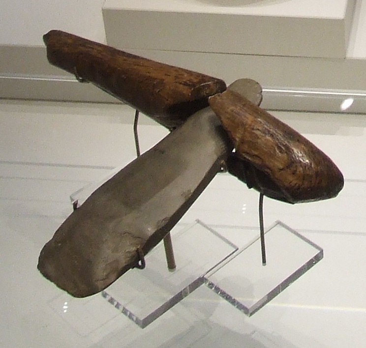A Neolithic stone axe with a wooden handle. Found at Ehenside Tarn, now in the British Museum