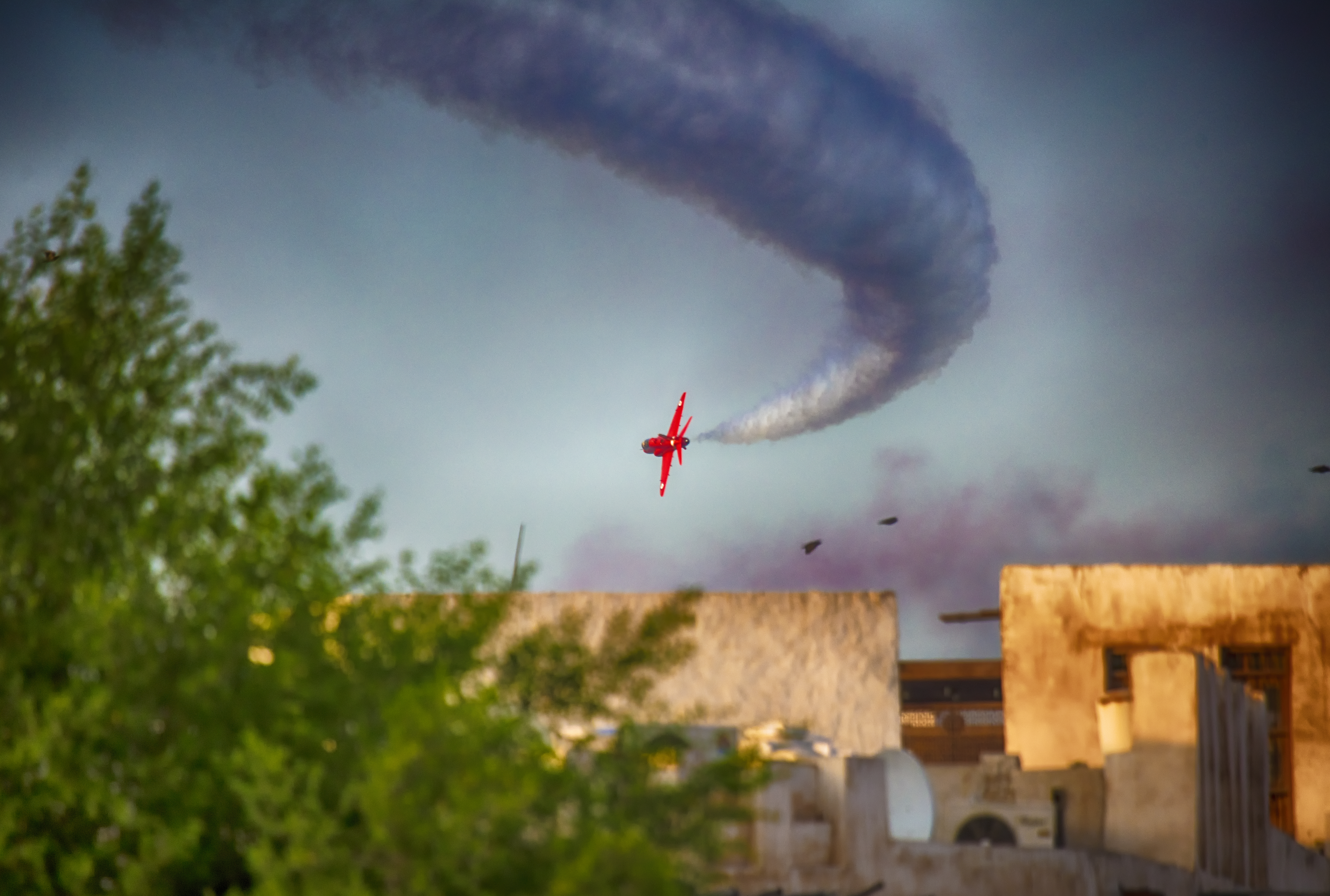 Red plane in the sky with contrail.jpg