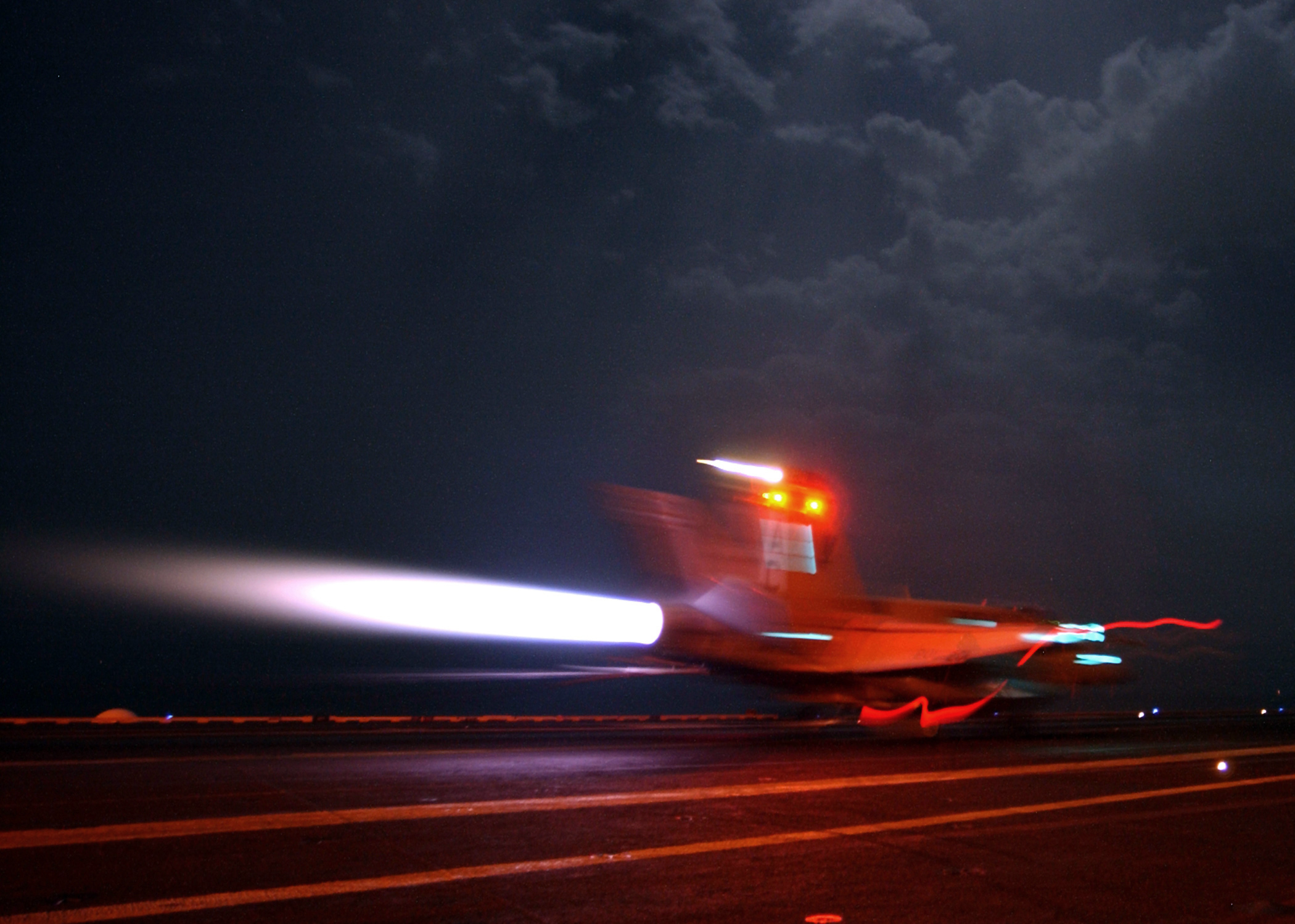 An aircraft lights its afterburners to maintain full power following an arrested landing aboard an aircraft carrier.