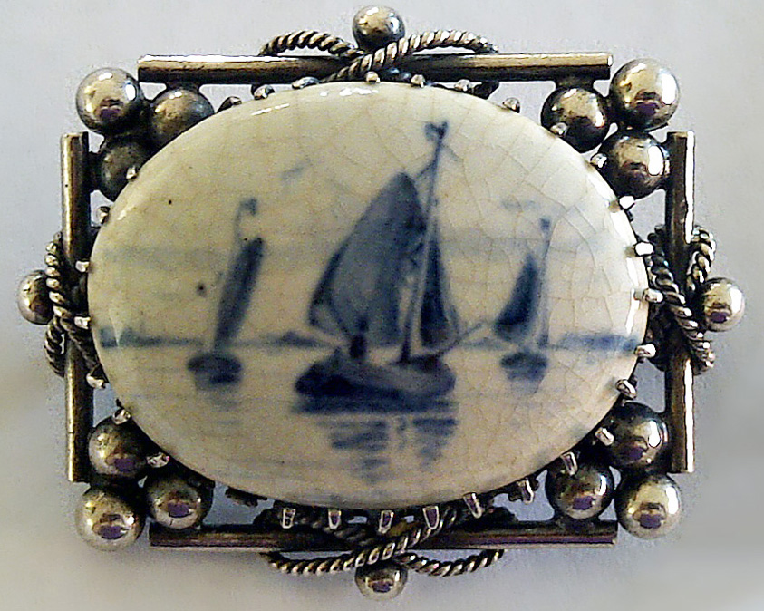 Ships brooch by De Porceleyne Fles of Delft with maritime inspired silver setting 1892