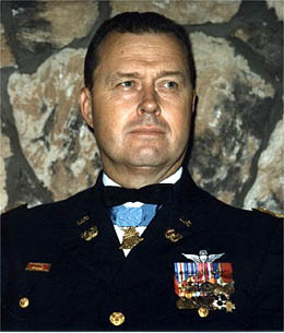 Head of a man with short, dark hair wearing a formal military uniform. Rows of ribbon bars and a winged pin are on his left breast, and a medal hangs from a light blue ribbon around his neck.