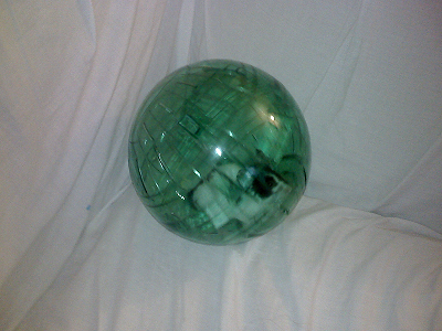 Photo of a white hamster in a transparent green plastic hamster ball