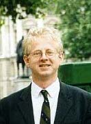 A blond man outside in glasses and a suit and tie