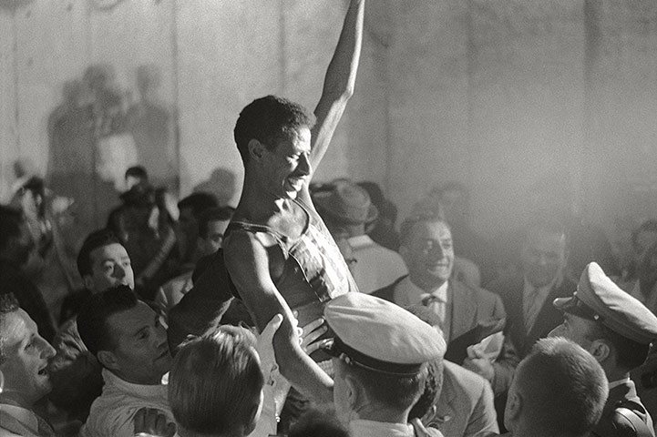 Abebe lifted above a crowd in celebration