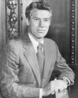 A man, in a business suit, sitting, facing the camera.
