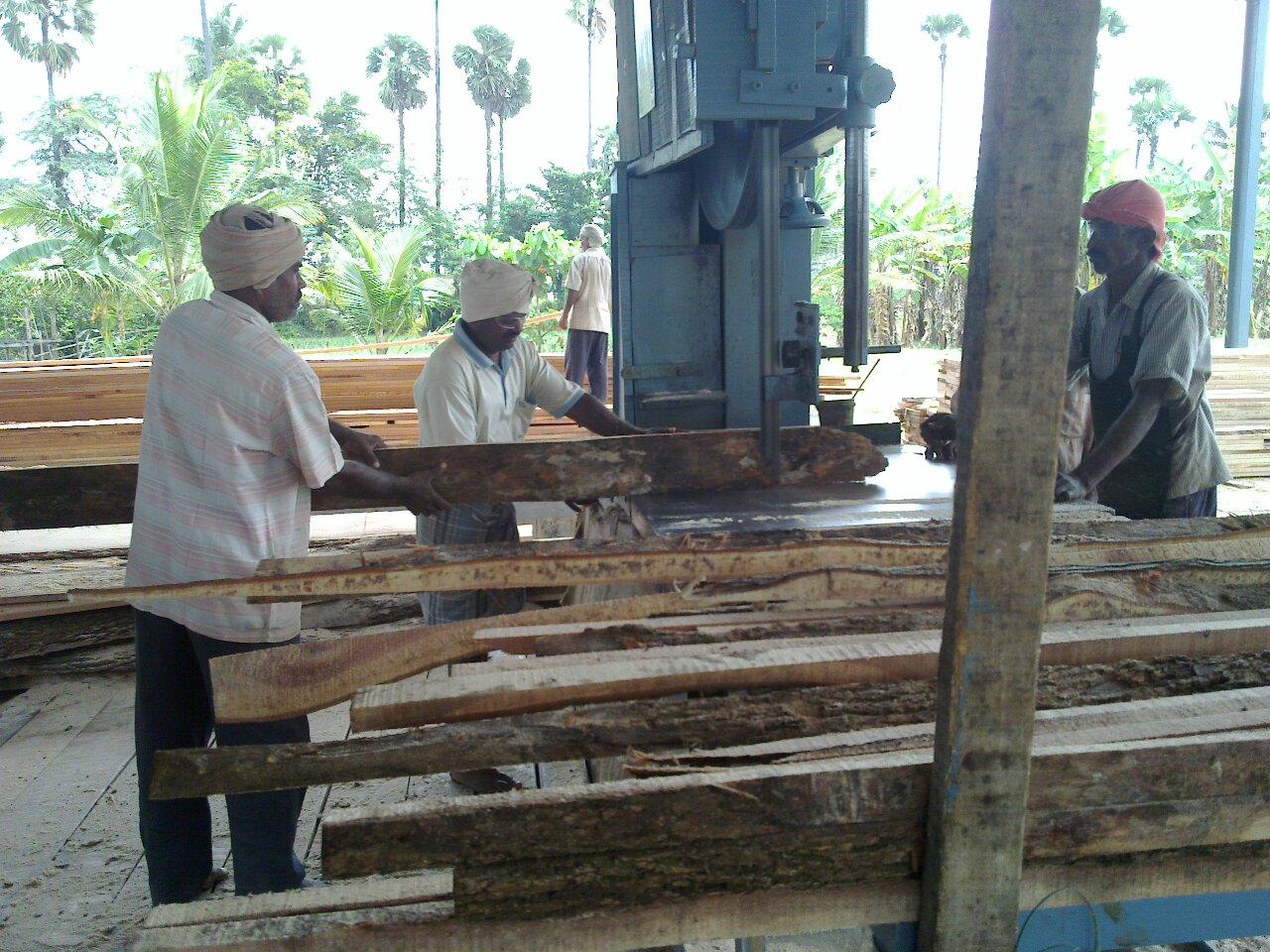 Three turbaned men passing rough wood through a saw