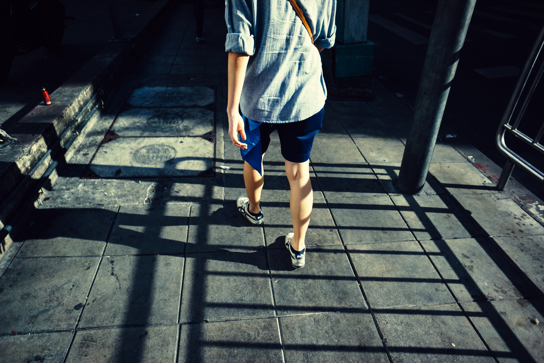 pessoa andando de tênis, shorts, uma camisa de manga longa e uma bolsa de ombro em Bangkok EXIF duração_exposição: 1/4000 · marca: Sony · iso: 100 · focal_length: