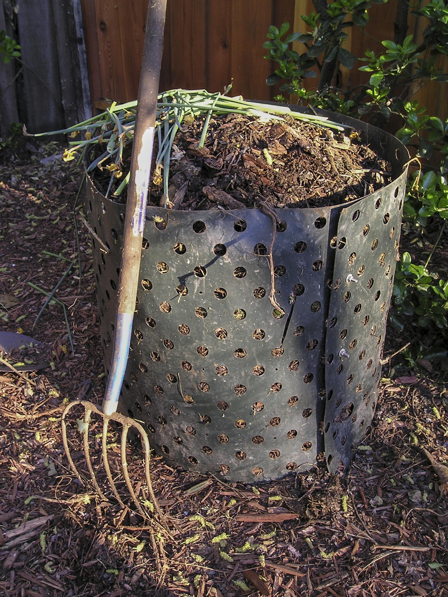 A pitchfork next to a compost bin