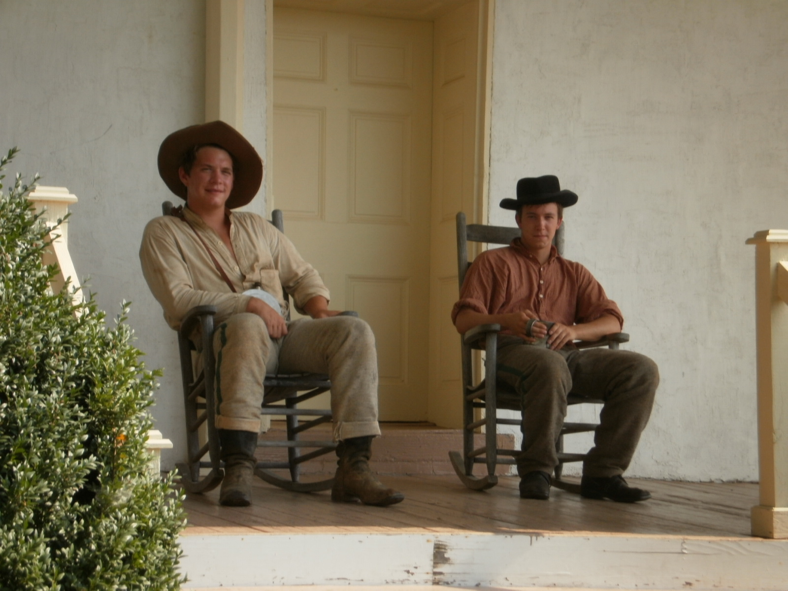 Two men in rocking chairs on a porch
