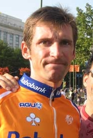 A man in his late twenties, wearing an orange and blue cycling jersey with white trim