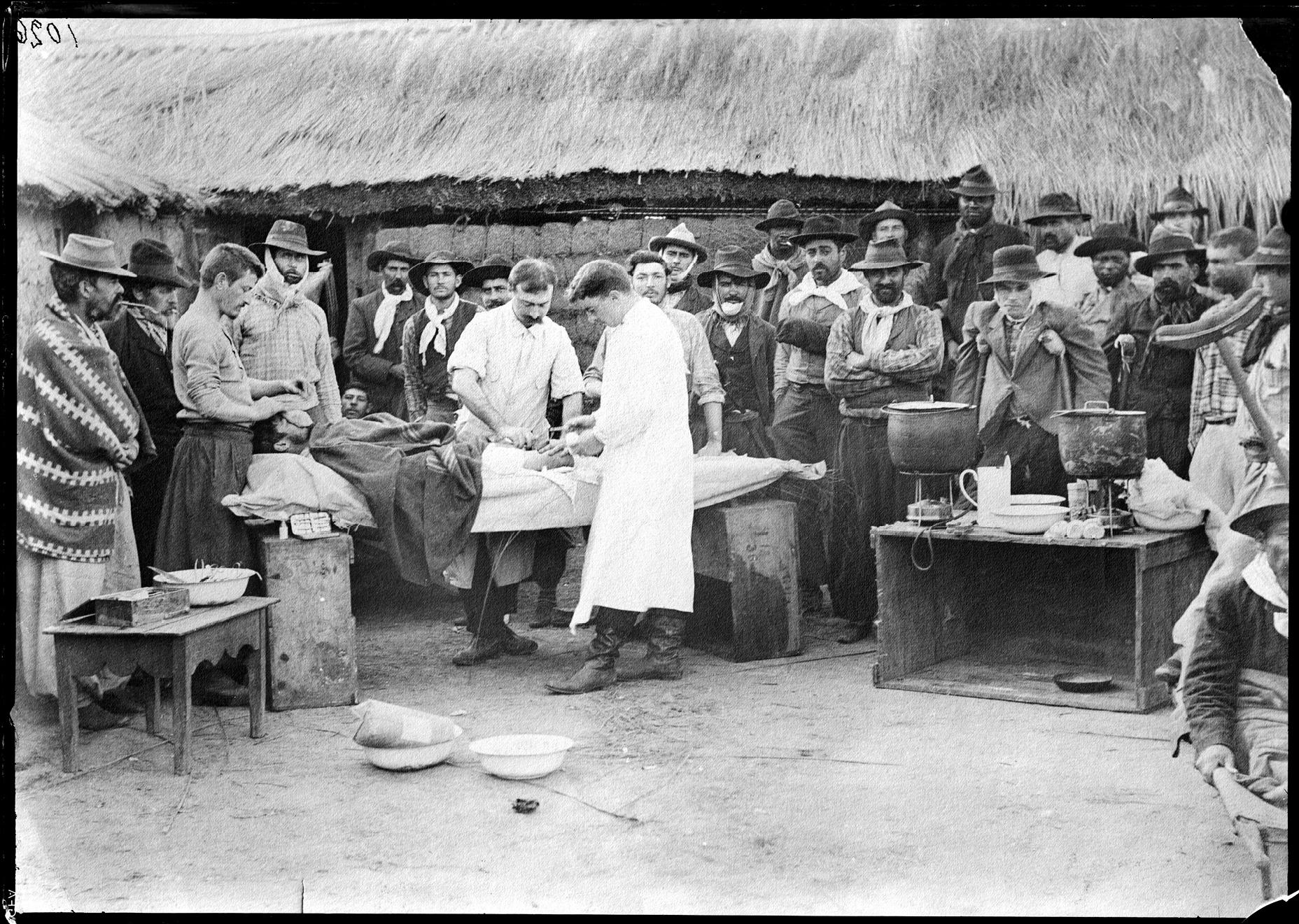 Intervención quirúrgica al aire libre llevada a cabo en el Hospital Nacionalista por los cirujanos miembros de la guardia médica de Aparicio Saravia: Baldomero Cuencas y Lamas y Bernardino Fonticiolla, durante la revolución de 1897.