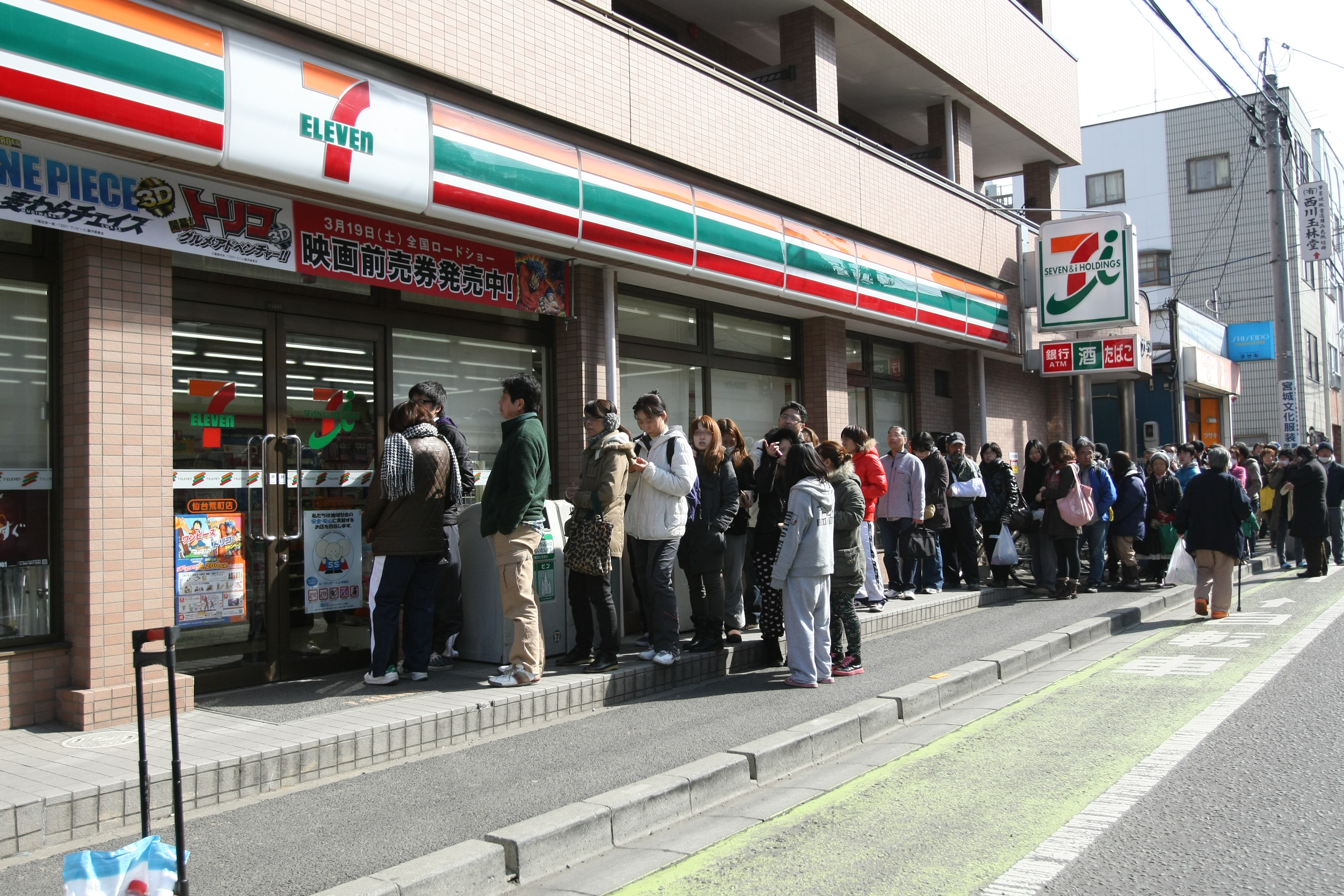 Japanese citizens queue up to receive basic food items after a earthquake.