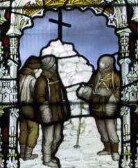 Drie figuren zijn afgebeeld in gekleurd glas, staande bij een sneeuwhoop met daarboven een groot kruis.  De scène wordt omlijst door een decoratieve boog.