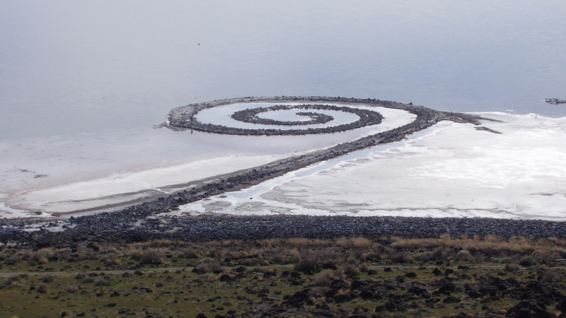 A stone jetty, curved in a spiral. Land art by Robert Smithson.
