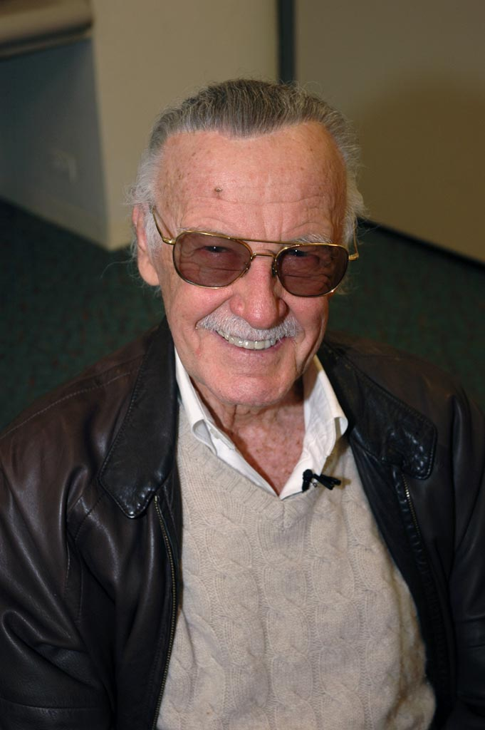 photo of Stan Lee, wearing aviator sunglasses, black leather jacket, grey cable-knit sweater, and white shirt open at collar. Photo by Edward Liu, courtesy of Wikimedia Commons.