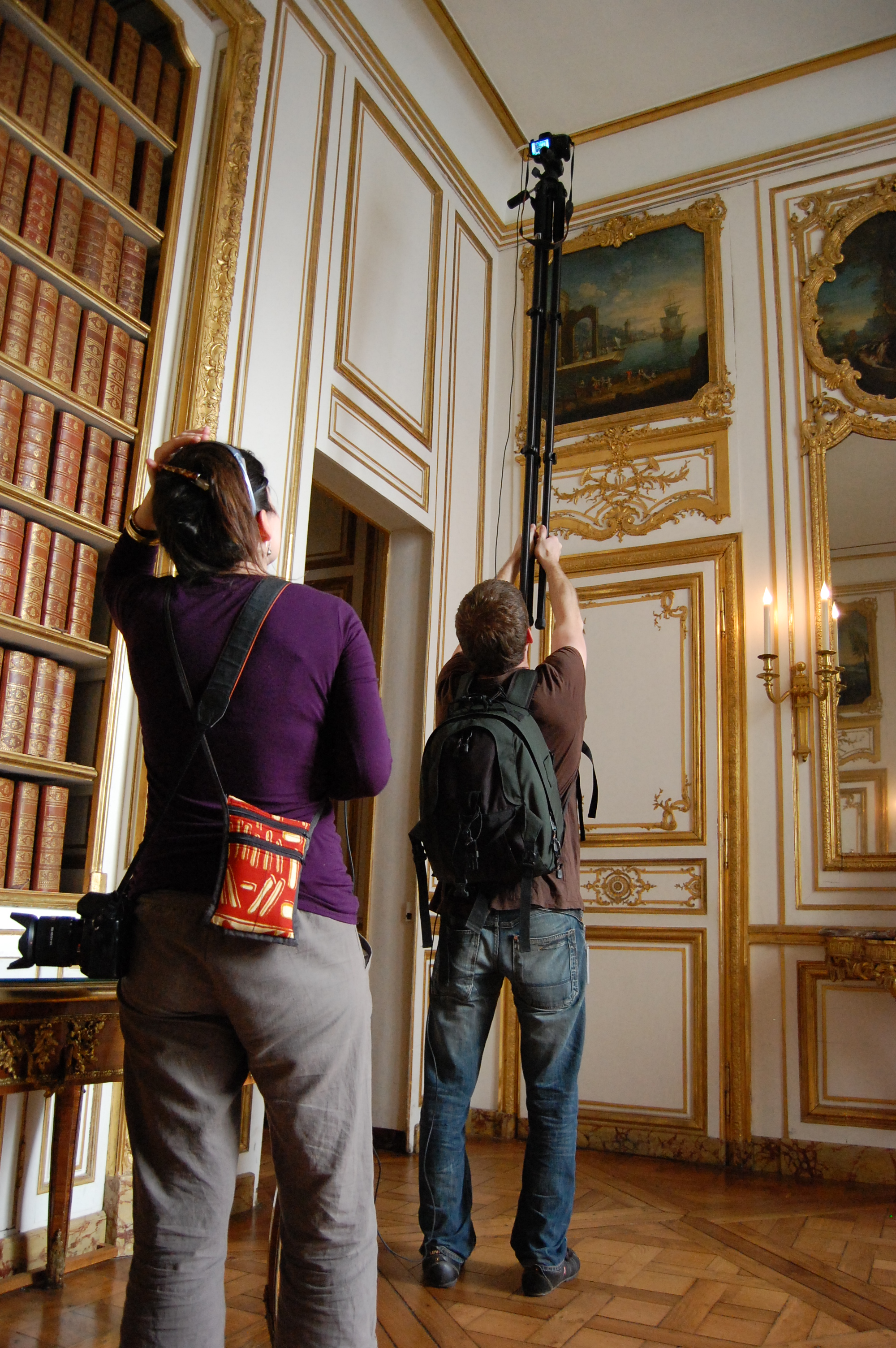 Two Wikimedians, with the aid of a pole, taking a photo of a painting installed several meters off the ground at the Palace of Versailles