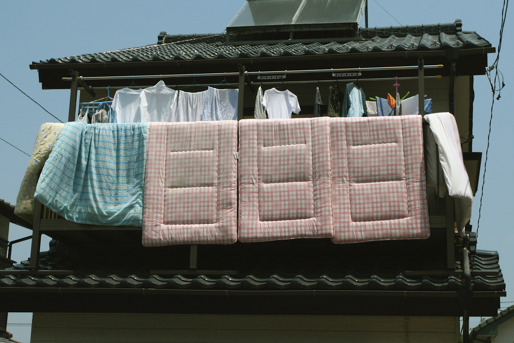 Picturing of clothes and futons being hung out to dry off of a balcony