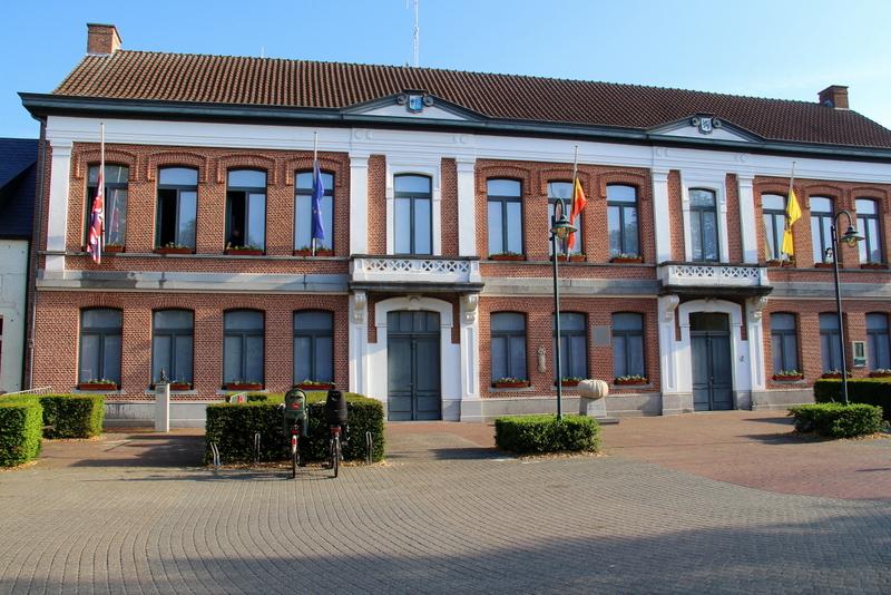 Voormalige onderwijzerswoning, in  874 (zie gevelsteen) verbouwd tot gemeentehuis en onderwijzerswoning naar ontwerp van L. Blomme. In 1995 uitgebreid als gemeentehuis en politiecommissariaat onder leiding van P. Bellemans, W. Steenhoudt en B. Robaye.