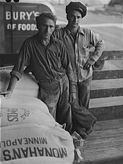 Two men who loaded flour and a bag of flour that says Monahan's Minneapolis and a Pillsbury truck