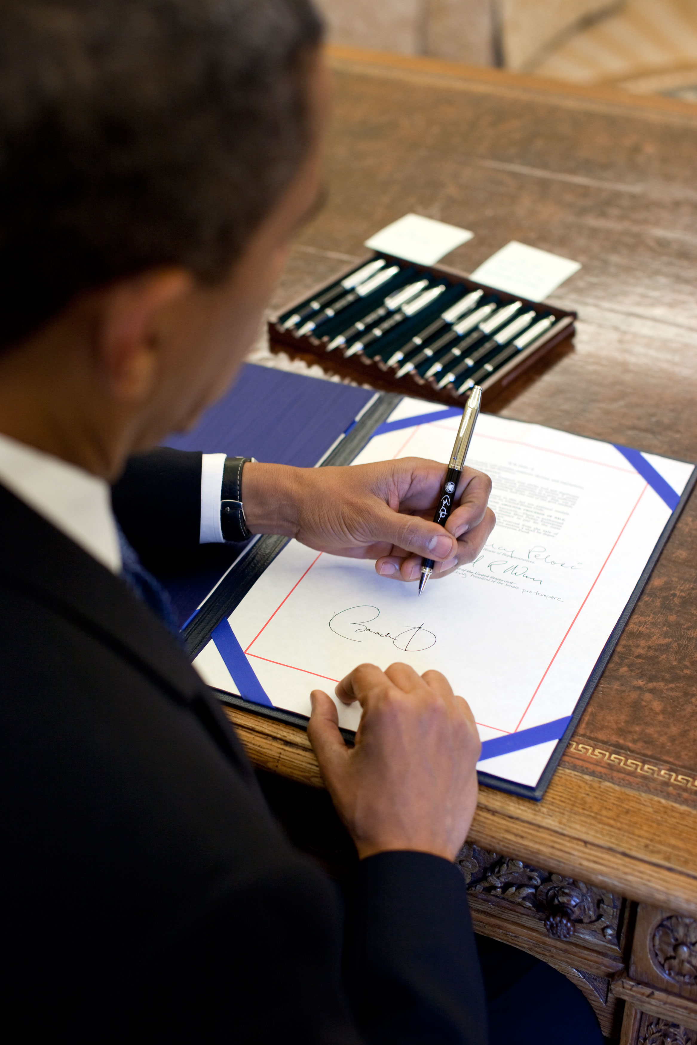 A shot over President Obama's right shoulder showing his signature after he has signed a bill into law.