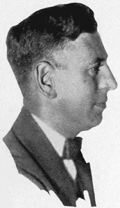 A black-and-white photograph of a middle-aged man with a short haircut. He wears a suit and tie, and faces left.