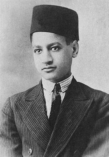 A boy wearing a jacket, a white shirt with a black tie and a fez on his head