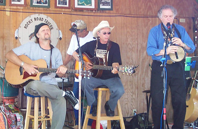 Joel Rafael (center) with Jimmy LaFave (guitar) and David Amram (flute) performing at the Woody Guthrie Festival in Okemah, OK. - July 15, 2006.