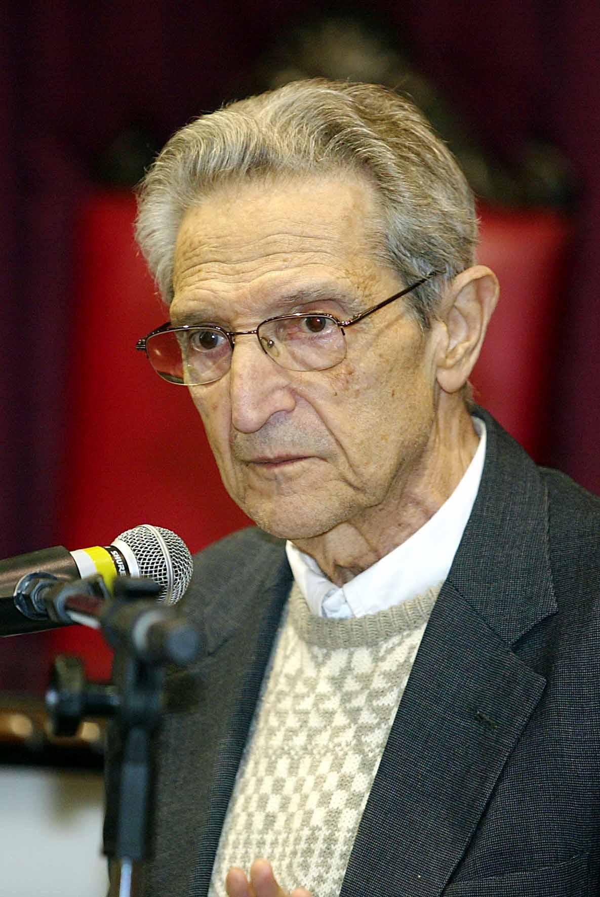 Senhor idoso de cabelos grisalhos, rosto enrrugado, óculos, utilizando paletó cinza escuro, suéter de lã claro e camisa social branca, à frente de um microfone, com uma cadeira fora de foco a vários metros atrás