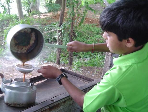 A boy preparing tea at a typical tea stall in India