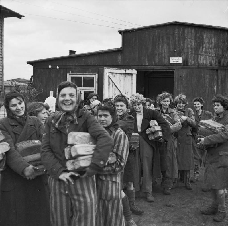 Smiling women holding aid parcels stand outside a hut at Bergen-Belsen concentration camp at its liberation by British forces.