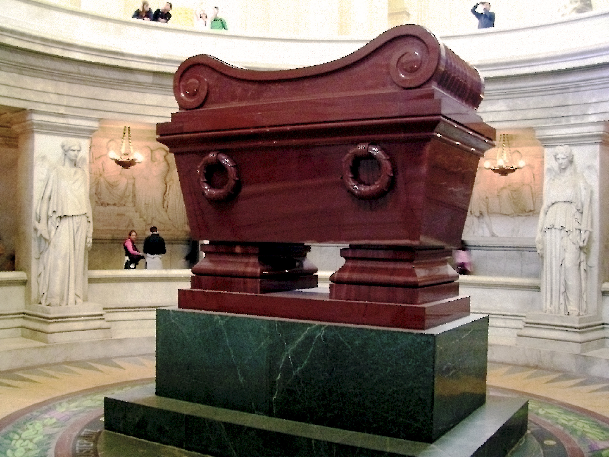 Photo of a large, shiny burgundy cuboid-shaped vessel raised on a dark green plinth. There are two female statues in the background either side of the vessel.