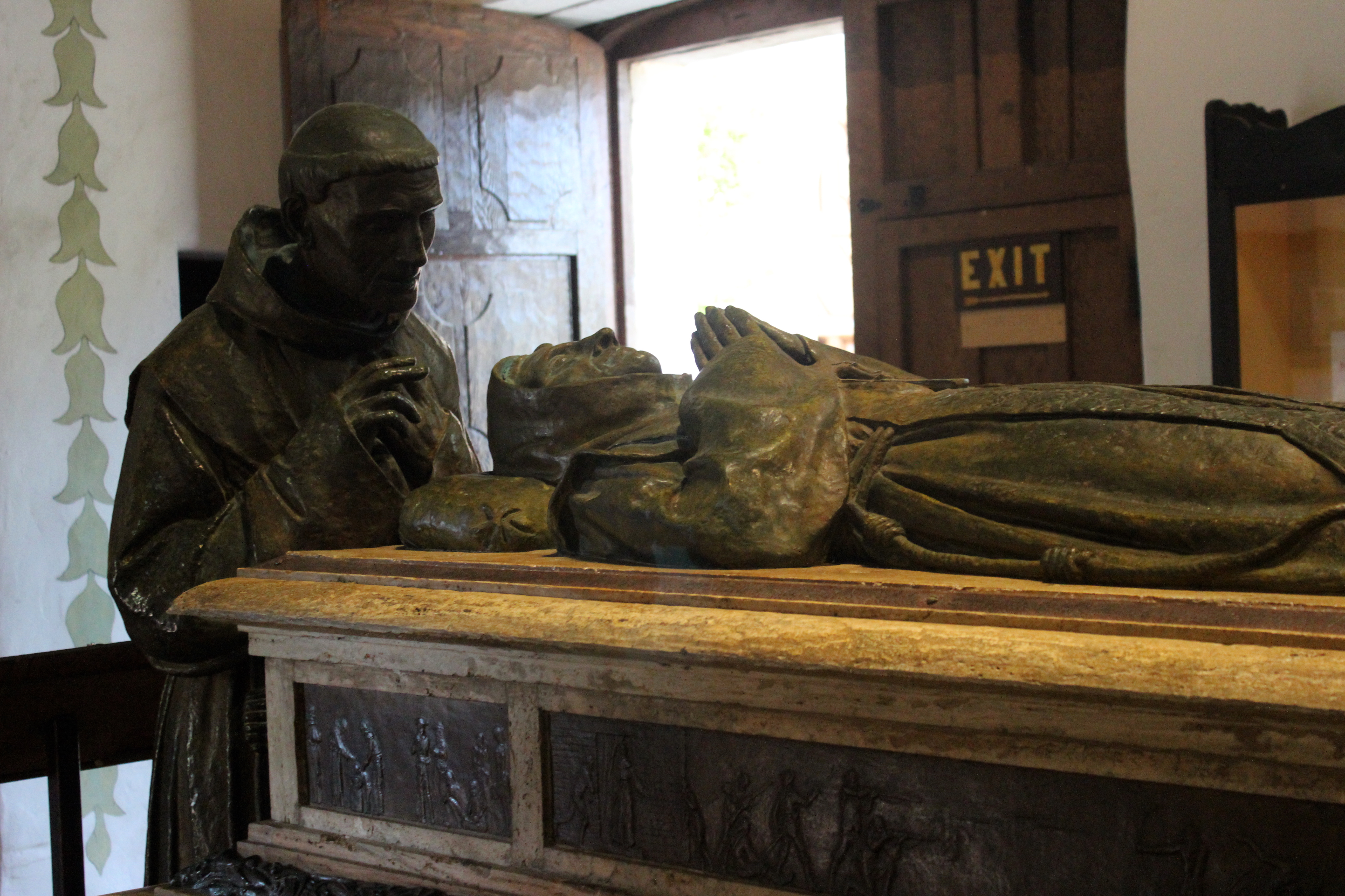 Cenotaph of Saint Junípero Serra in the Mission San Carlos Borromeo, Carmel-by-the-Sea (1924); Fr. Juan Crespí, who predeceased Serra, stands at the head, praying over him.
