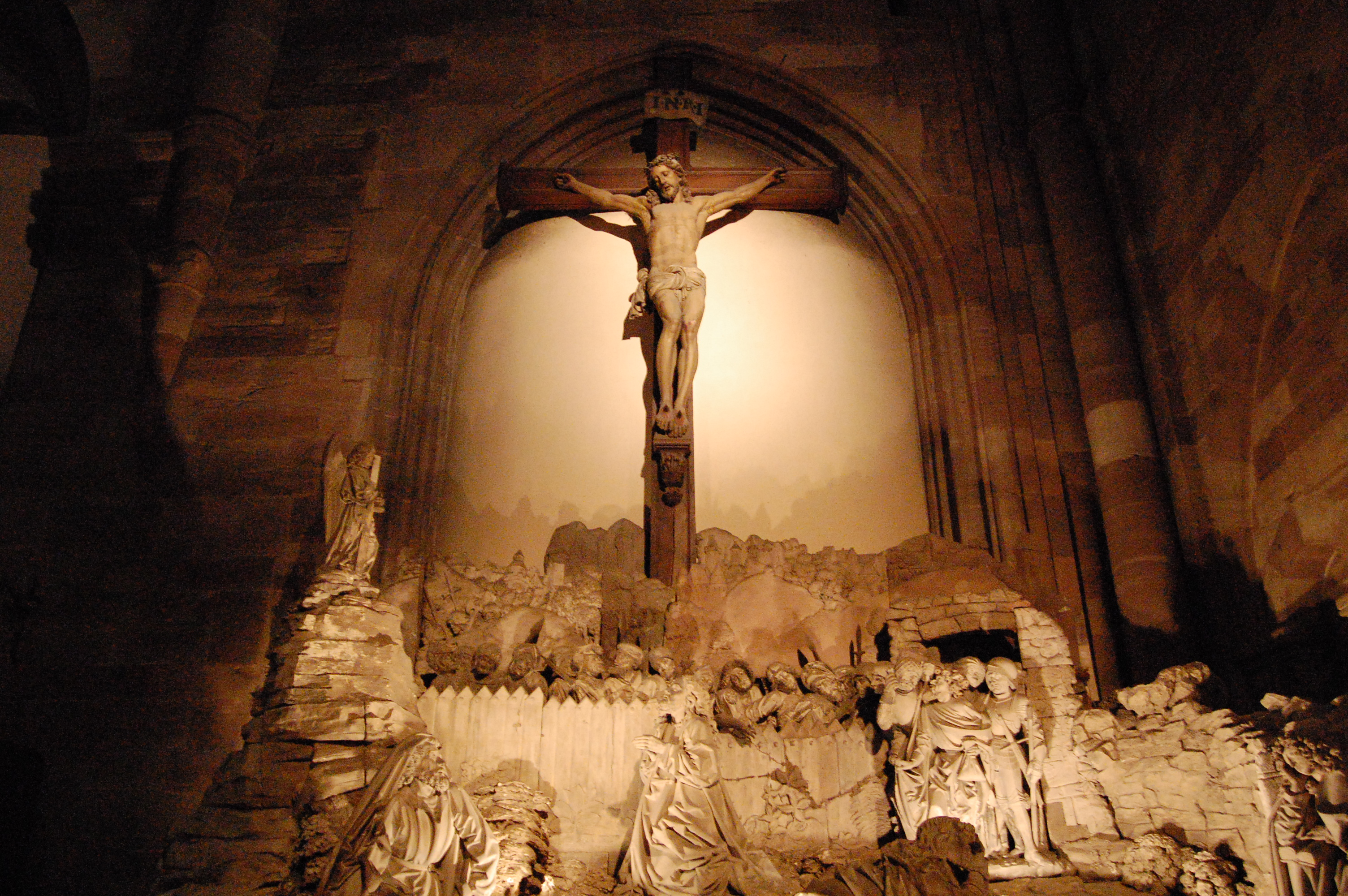 A crucifix hanging over a carved crowd of figures below it