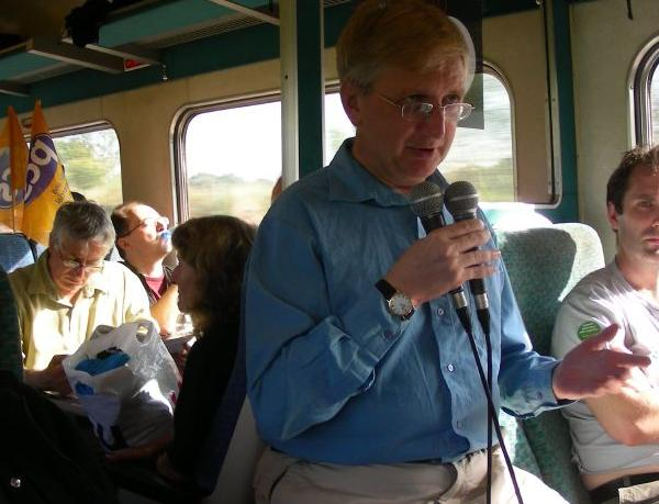 Craig Murray holding two microphones