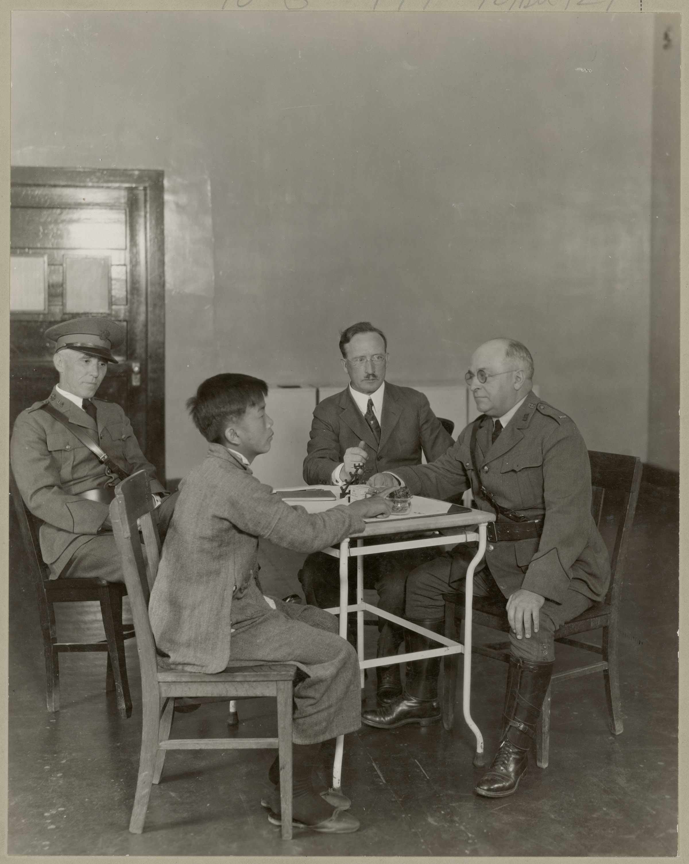 1923 photo of Chinese immigrant undergoing immigration interview with three US officials on Angel Island