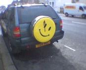Lo smiley macchiato di sangue che compare più volte nel corso di Watchmen, ritratto sul retro di una jeep.