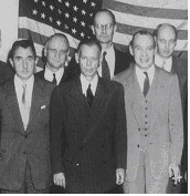 Six standing men in suits and ties. A forty eight-star American flag covers the wall behind them.