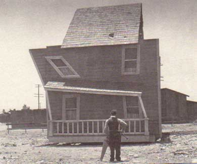 Buster Keaton looking at a poorly constructed house