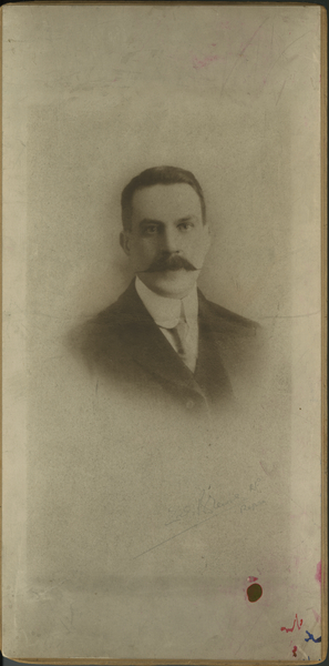 File:Photograph, sepia, of the head and shoulders of a man. Short, dark, hair, 'handle-bar' moustache, high collar. Pencil name on left hand bottom corner. Red ink blot and red and blue marks on left (15406993963).jpg