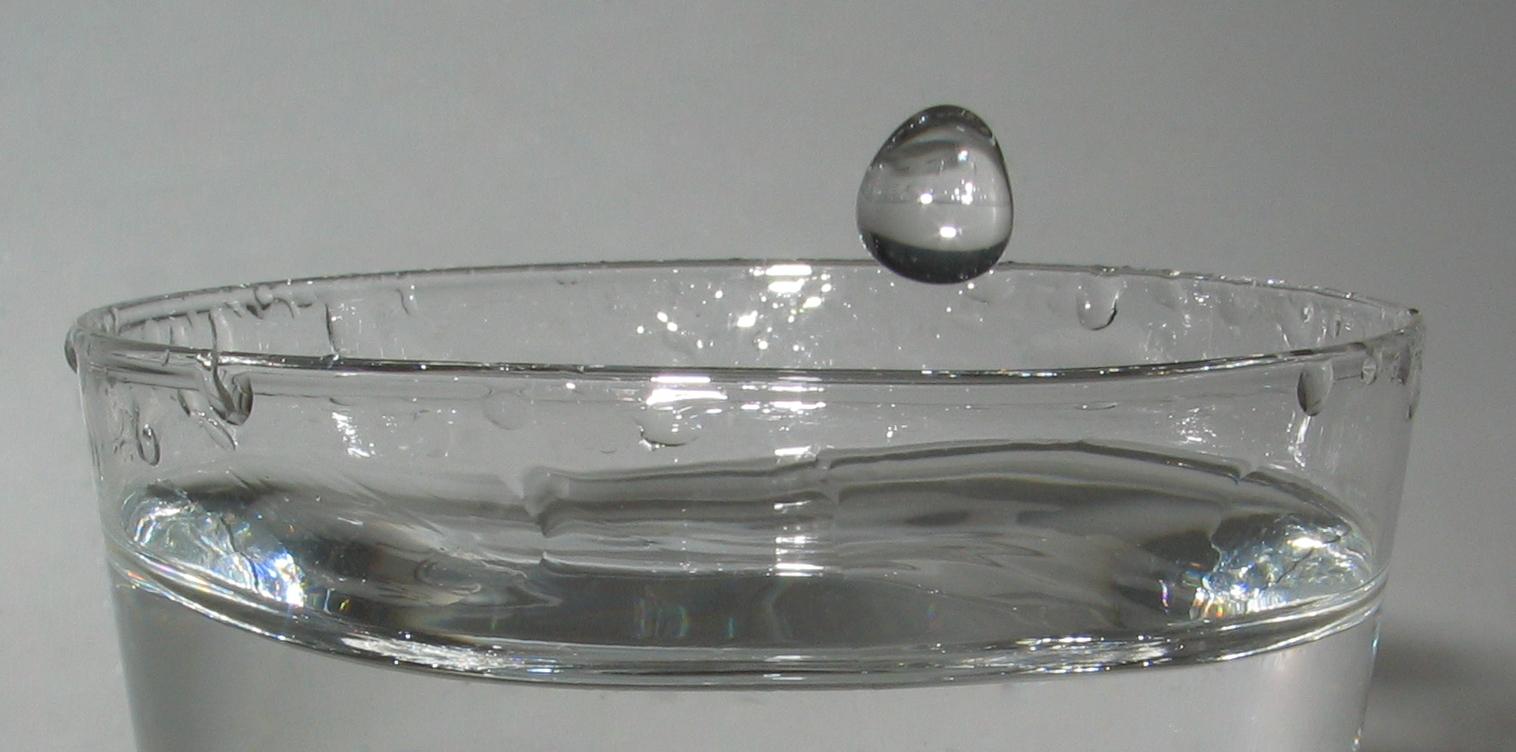 Gota de agua, antes de impactar en un vaso lleno de agua.