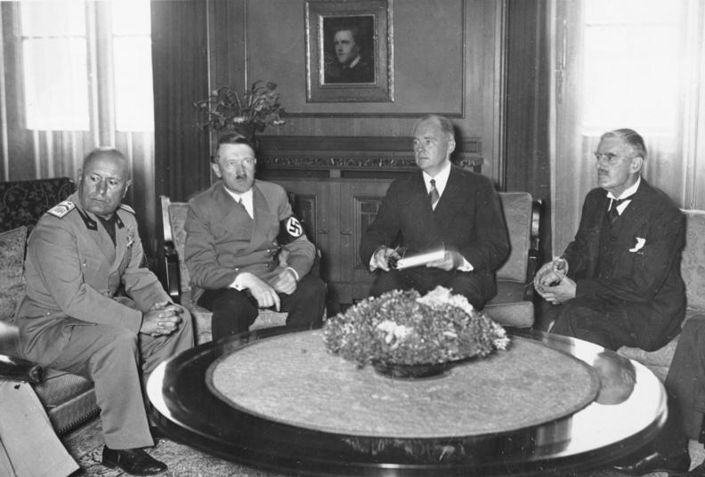 De izquierda a derecha: Benito Mussolini, dictador de Italia; Adolf Hitler, dictador de Alemania; Neville Chamberlain, primer ministro de Reino Unido; y Paul Otto Gustav Schimdt, traductor e intérprete alemán, durante la firma de los Acuerdos de Munich y que pusieron fin al papel de las Brigadas Internacionales. Autor: Desconocido, 30/09/1939. Fuente: Bundesarchiv, Bild 146-1970-052-24 (CC-BY-SA 3.0.)
