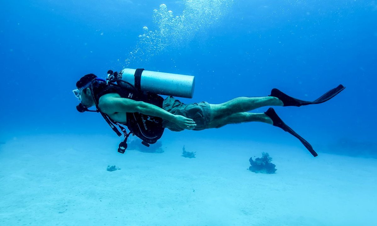 A scuba diver with gear in ocean bed