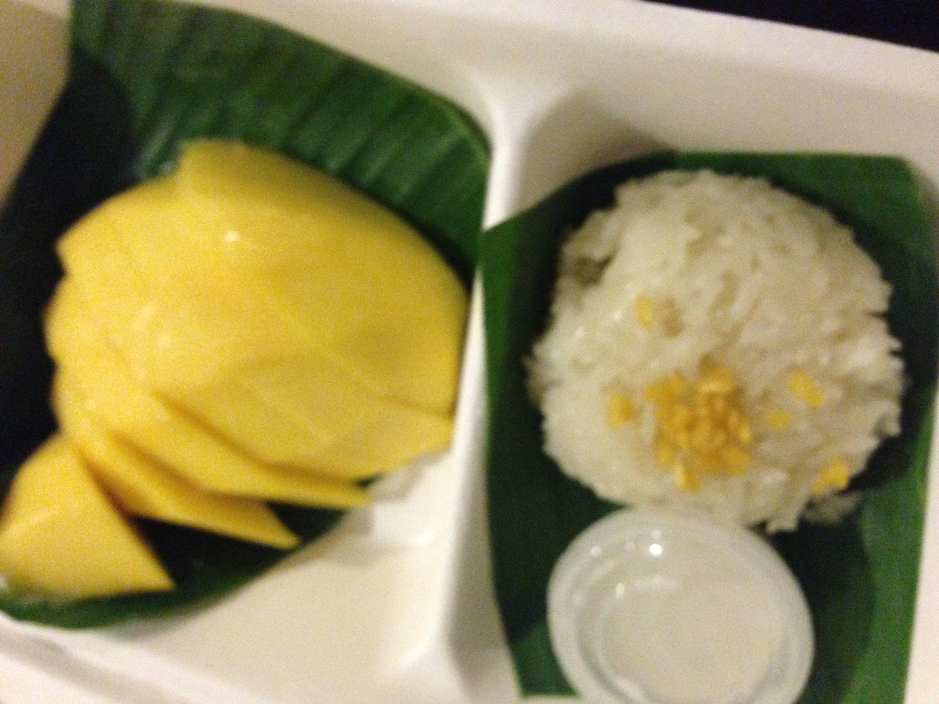Slices of mango and a scoop of sticky rice on separate leaves