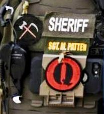 "Detail of one soldier's uniform, showing a patch with a black ""Q"" on a red background, and a second patch with a black field bearing an axe and scythe crossed over one another"