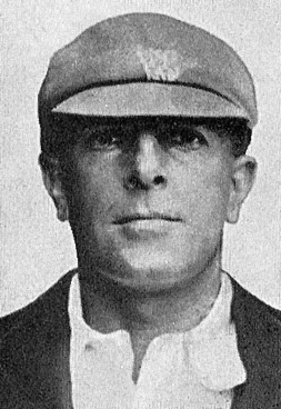 Portrait of man from just below the shoulder upwards. He is wearing a light shirt and blazer over the top, a cricket cap, dark with a white crest. The resolution is poor and nothing more of the crest can be discerned. He is unshaven and staring at the camera, not smiling.