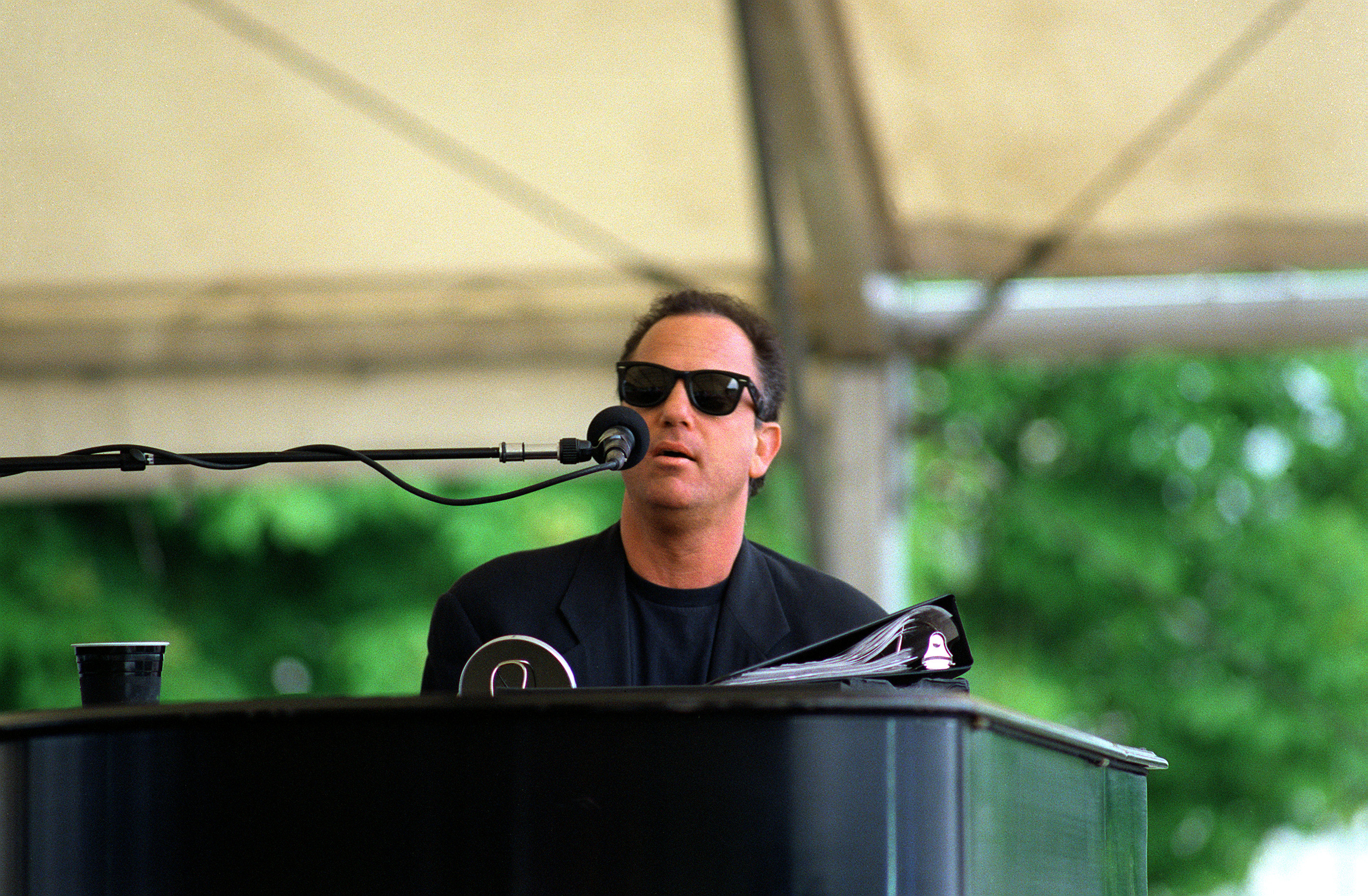 Billy Joel playing piano outdoors at the USO concert in 1994.
