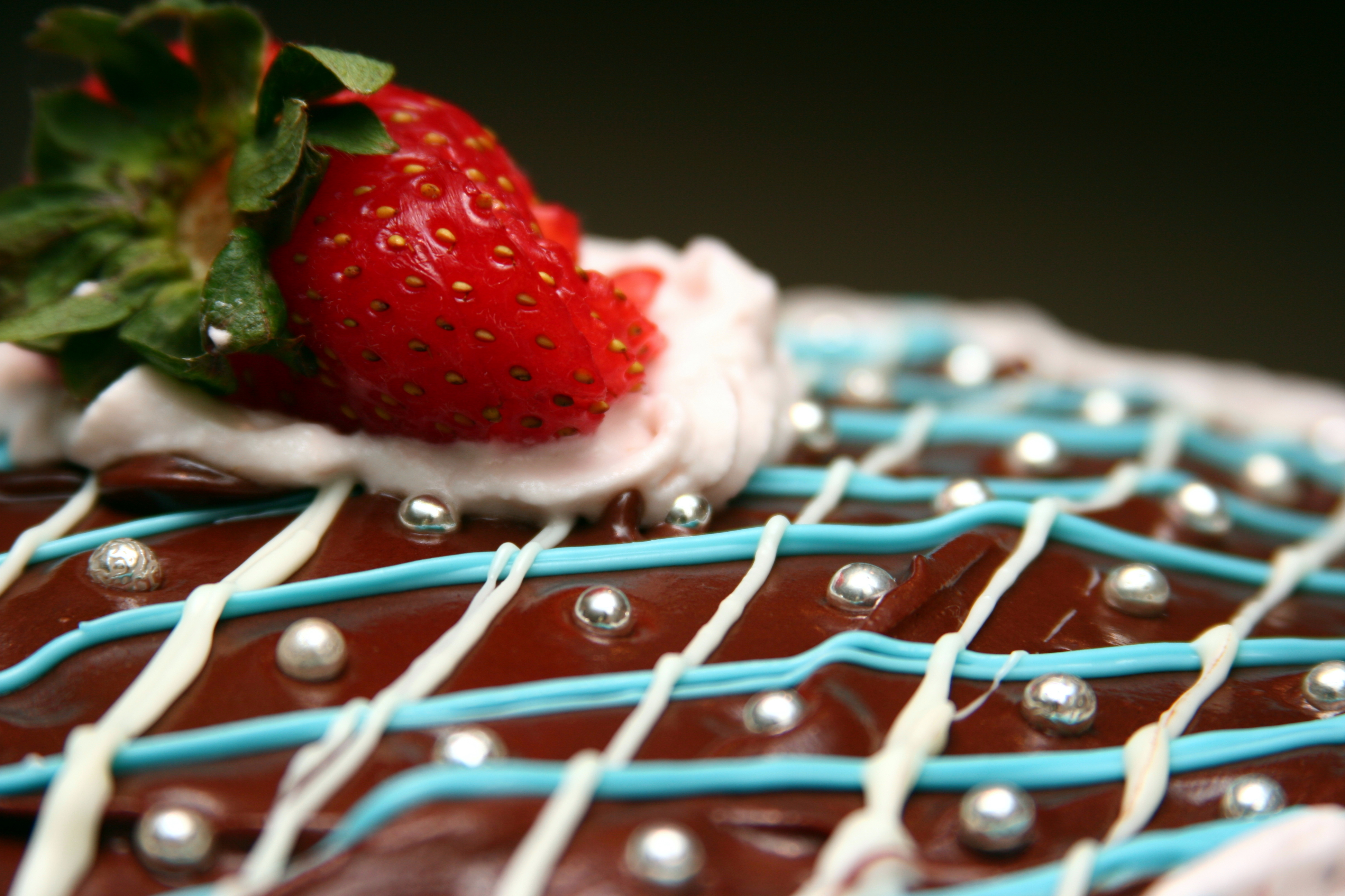 chocolatecakedecoratedwithicing,strawberries,andsilverysugarbeadsorrageetallicrages.