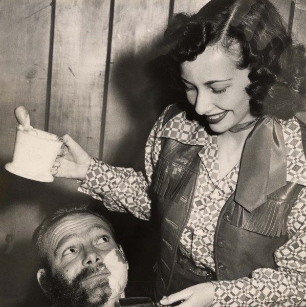 A photo of a lady giving her man an old fashion shave, to help him be more groomed.